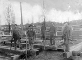 [A group of men building a wooden structure beside a cemetery]