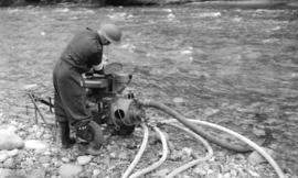 [A.R.P. fireman using a portable pump at Lynn Creek]