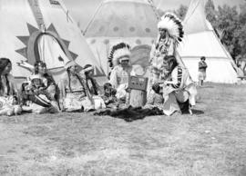 [Stoney Indian group listening to a radio on Calgary Stampede grounds]