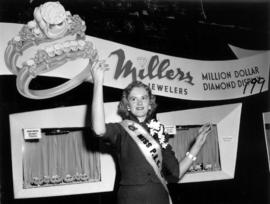 Miss P.N.E., Glenda Sjoberg, holding up rings at Millers Jewelers display in Manufacturers building