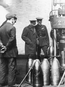 [King George inspects a press at a munitions factory]