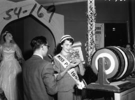 Nancy Hansen, Miss P.N.E., holding necklace at Millers Jewelers draw in Manufacturers building