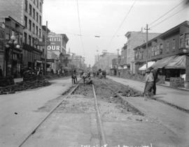 [Men laying streetcar tracks at Granville and Davie Streets, for reconstruction of Granville Stre...