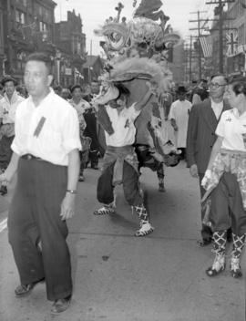 [Men with Chinese lion in a Victory celebration parade through Chinatown]
