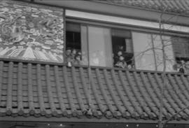 Chinese New Year parade spectators at window above Yuen Fong Co. Ltd. store on Pender Street