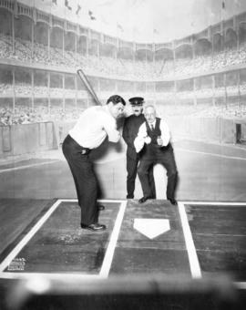 [Babe Ruth on Pantages Theatre stage about to swing bat, with Mayor L.D. Taylor as catcher and Ch...