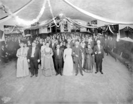 [An unidentified group dressed in formal attire in a hall decorated with streamers]