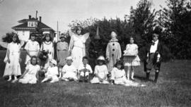 [Children in costumes on a lawn in front of a house]