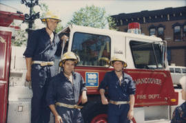 Firefighters standing next to fire engine