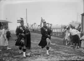 Bagpipers in front of a pier with a small crowd of spectators