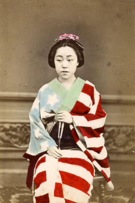 [Studio portrait of a woman in formal Japanese dress sitting on a chair holding a fan]