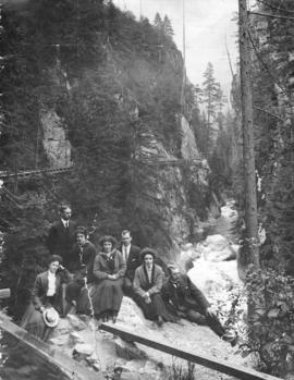 [Men and women on rock at Capilano Canyon]
