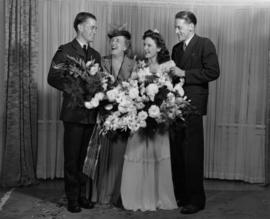 Hugh Pickett with two women and a man holding flowers