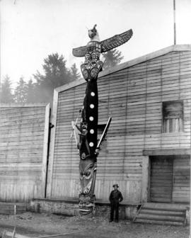 Man standing beside Kwakwaka'wakw Totem Pole outside of Longhouse
