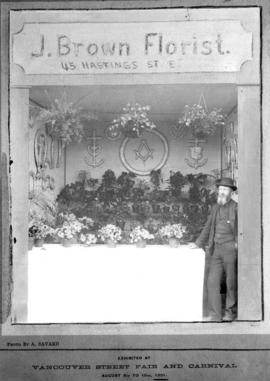'J. Brown Florist' booth at Vancouver street fair and carnival, with Joseph Brown at right