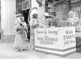 [Stoney Indians buying war stamps at a war savings booth on the street]