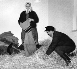 [Hungarian refugees prepare a bed in straw in the Immigration Building at the airport]