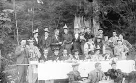 [Men and women eating strawberries at a picnic in Stanley Park]