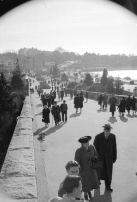[People strolling along Stanley Park causeway near the park entrance]