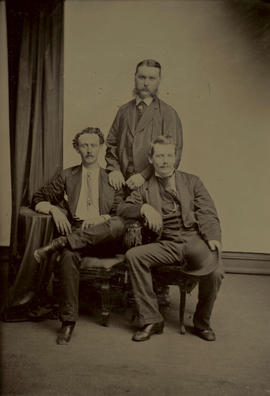 [Studio portrait of three men, one standing, two seated]