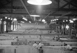 [Interior view of the Boeing plant on Sea Island showing workers assembling airplane parts]
