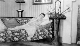 Woman lounging on couch beside wicker basket of lilies