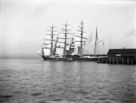 Square rigged ships at a dock