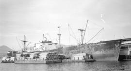 S.S. Leonadis Michalos [at dock, with lumber-filled barges alongside]