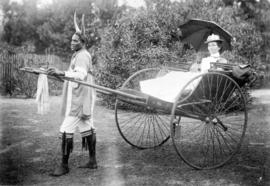 Miss Minnie Affleck riding in a ricksaw drawn by a costumed Khaffir