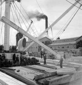 [Workers loading lumber onto a boat at the H.R. McMillan Co.]