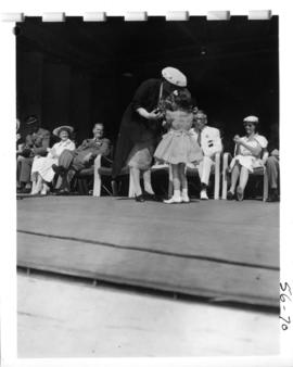Girl presenting Mrs. W.A.C. Bennett with flowers on Outdoor Theatre stage during 1956 P.N.E. Open...