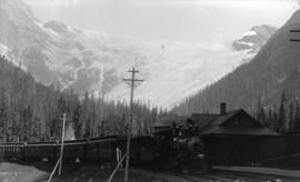 [Passenger train stopped at station in mountains]