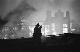 Denman Arena fire with silhouettes of firefighters in the foreground