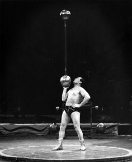 Strongman balancing barbell with one hand in Moscow Circus performance