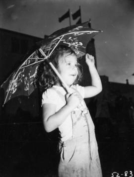 Young girl with umbrella standing by the P.N.E. Forum