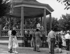Band playing in bandstand and onlooking crowd