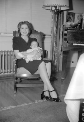 [Mrs. A.G. Duncan Crux, formerly Miss. June Roper, with a baby on her lap]