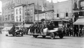 [Wartime parade showing a military band and a Great War Veterans float in the 100 Block of East H...