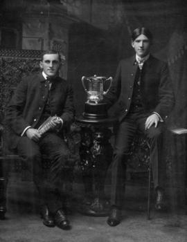 Portrait of two young Vancouver firemen seated beside silver trophy