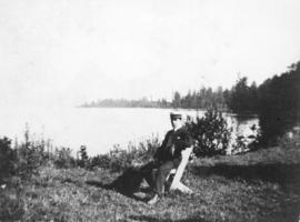 [Man sitting in folding chair near shore of Stanley Park]