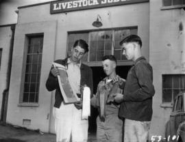 Boys holding 4-H competition prizes outside of Livestock Judging building