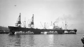 S.S. Lakonikos [at dock, with lumber-filled barges alongside]