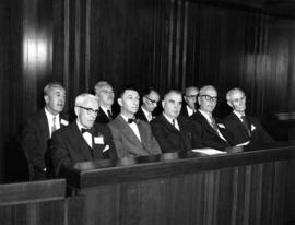 Group of men seated in council chambers for 75th anniversary special council meeting
