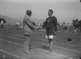 Athlete holding discus shaking hands with official