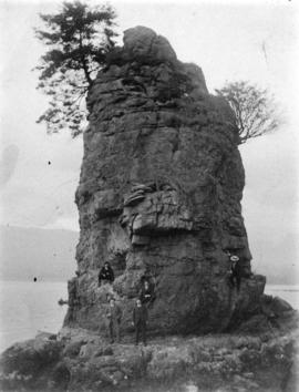 [View of six men at rock formation known as Siwash Rock, Stanley Park]