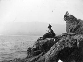 [Woman sitting on rock formation known as Siwash Rock's wife, sketching]