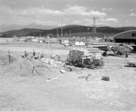 [View of Cranbrook airport showing water bomber by airplane hanger and crews in the foreground pr...