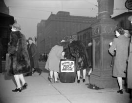 "[Pedestrians on Georgia Street walking by a barrel with a sign reading ""It's Friday the..."