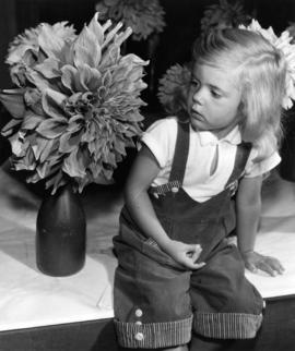 Young girl sitting with horticultural display at 1959 P.N.E. Horticultural Show