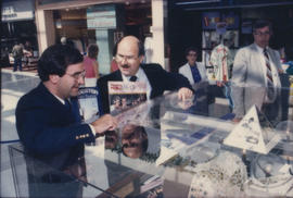 Unidentified man and Mike Harcourt standing beside display case